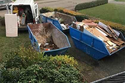 RÜMPLIO bei einer Entrümpelung eines Einfamilienhauses. Im Bild sind 3 Container zu sehen und ein Transporter.