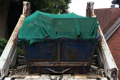 Auf dem Bild ist ein Container auf einem LKW zu sehen. Der Container ist bei einer Entrümpelung zum Einsatz gekommen um den Müll entsorgen zu können.
